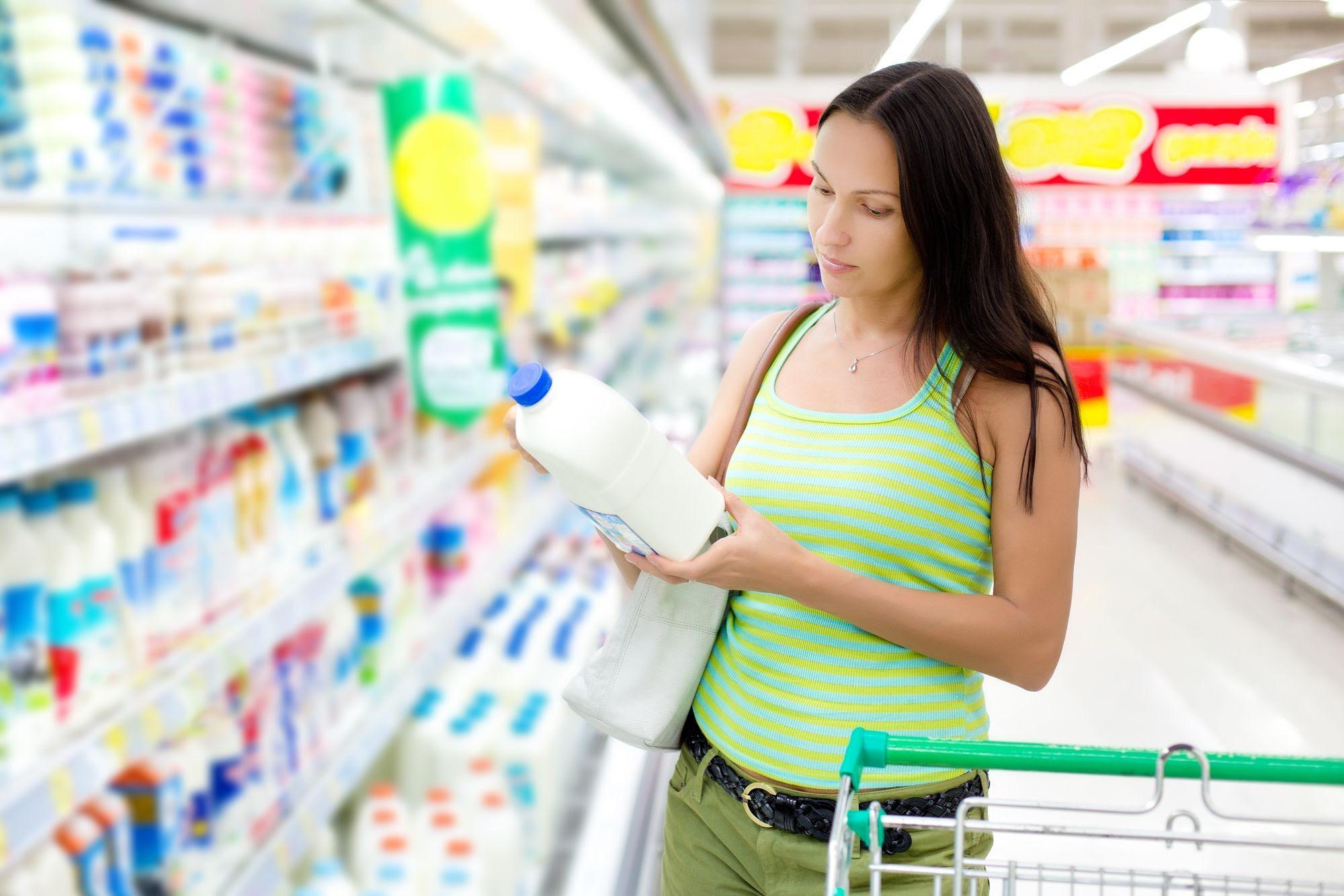 женщина в магазине покупает пастеризованное молоко